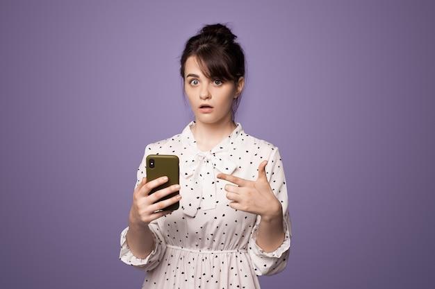 Geschokt kaukasische brunette vrouw wijzend naar haar telefoon poseren op een violette studio muur