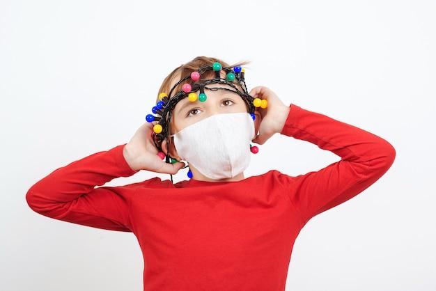 Geschokt kind dat veiligheidsmasker draagt. moe kind met feestelijke slinger tijdens quarantaine. coronapandemie. ongelukkige jongen met negatieve emoties