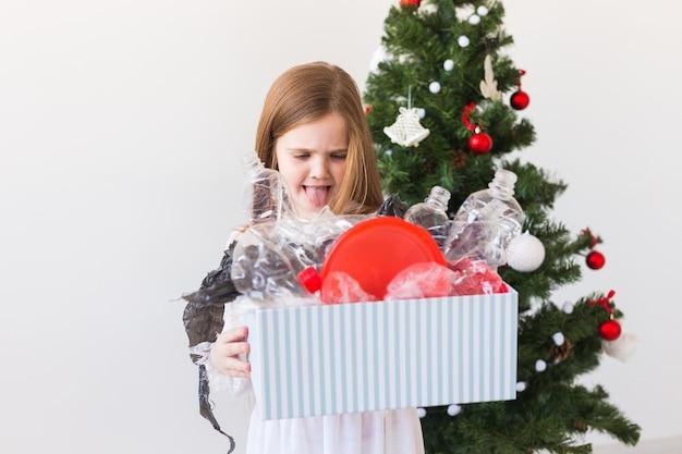 Geschokt kind meisje kijkt met geopende ogen en bezorgde uitdrukking met doos met afval