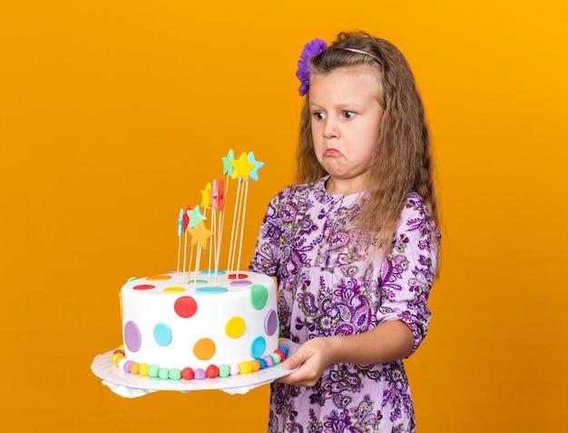 Geschokt klein blond meisje houdt en kijkt naar verjaardagstaart geïsoleerd op een oranje muur met kopieerruimte