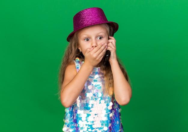 Geschokt klein blond meisje met paarse feestmuts hand zetten mond praten over telefoon geïsoleerd op groene muur met kopie ruimte
