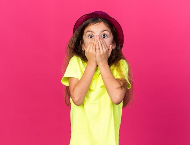 Geschokt klein kaukasisch meisje met paarse feestmuts handen op de mond zetten geïsoleerd op roze muur met kopie ruimte
