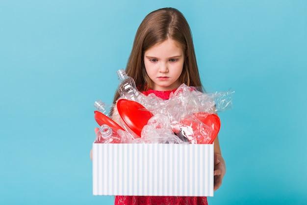 Geschokt klein kind meisje kijkt met geopende ogen met doos met afval