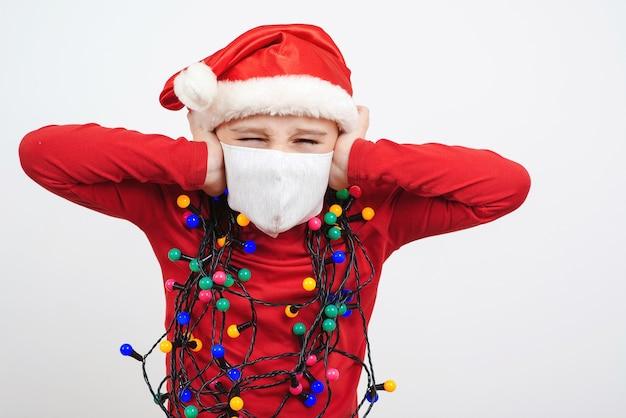 Geschokt klein santakind dat het masker van het veiligheidsgezicht draagt. moe kind in satna hoed en feestelijke slinger.