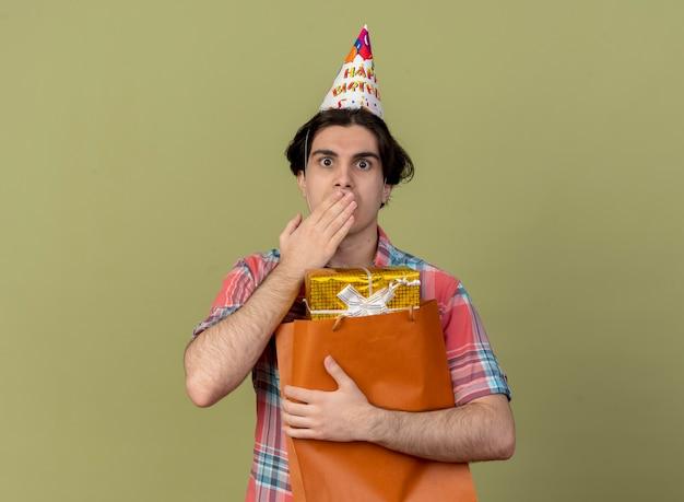 Geschokt knappe blanke man met verjaardagspet legt hand op mond en houdt geschenkdoos in papieren boodschappentas