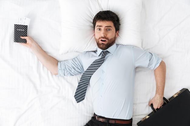 Geschokt knappe jonge zakenman in de ochtend in bed ligt bedrijf paspoort
