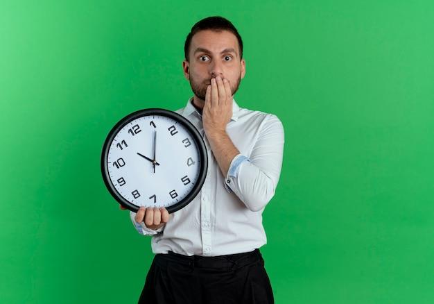 Geschokt knappe man houdt klok en legt hand op mond geïsoleerd op groene muur