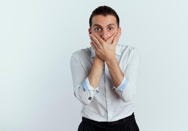 Geschokt knappe man houdt mond met twee handen geïsoleerd op een witte muur