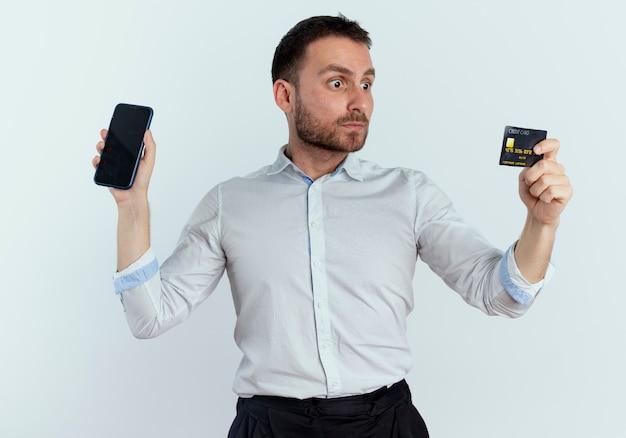 Geschokt knappe man houdt telefoon vast en kijkt naar creditcard geïsoleerd op een witte muur