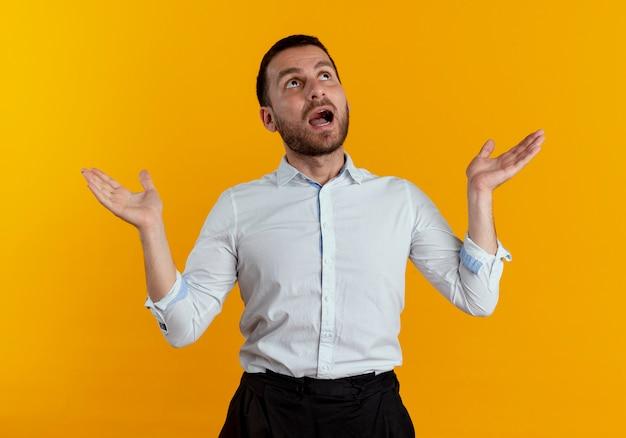 Geschokt knappe man kijkt met opgeheven handen geïsoleerd op een oranje muur