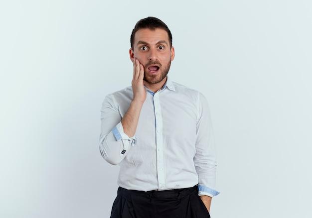 Geschokt knappe man legt hand op gezicht op zoek geïsoleerd op een witte muur
