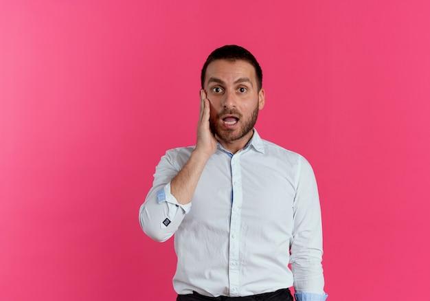 Geschokt knappe man legt hand op gezicht op zoek geïsoleerd op roze muur