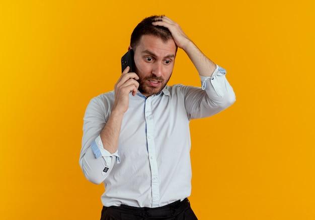 Geschokt knappe man legt hand op hoofd praten over telefoon geïsoleerd op oranje muur
