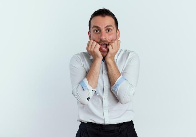 Geschokt knappe man legt handen op gezicht op zoek geïsoleerd op een witte muur