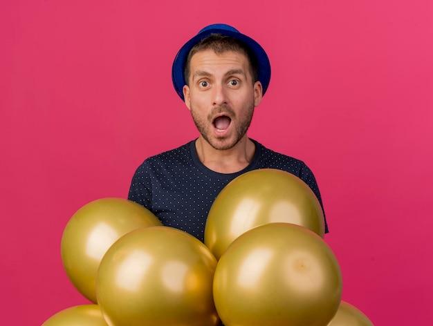 Geschokt knappe man met blauwe feestmuts houdt helium ballonnen geïsoleerd op roze muur met kopie ruimte