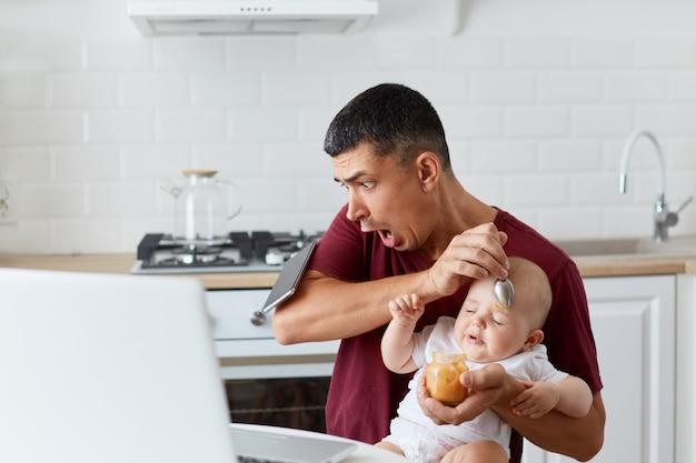 Geschokt knappe man met kastanjebruin casual t-shirt laat smartphone vallen terwijl hij aan tafel in de keuken zit en kleine dochter of zoon voedt, bang vader met babyjongen of meisje.