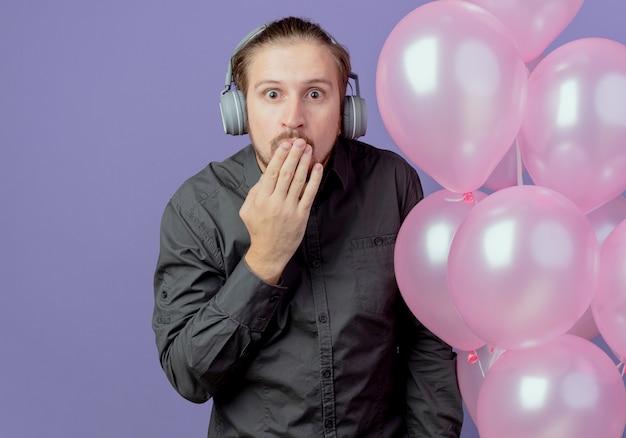 Geschokt knappe man op koptelefoon staat met helium ballonnen hand op mond zetten geïsoleerd op paarse muur