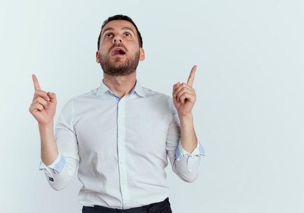 Geschokt knappe man op zoek en omhoog met twee handen geïsoleerd op een witte muur