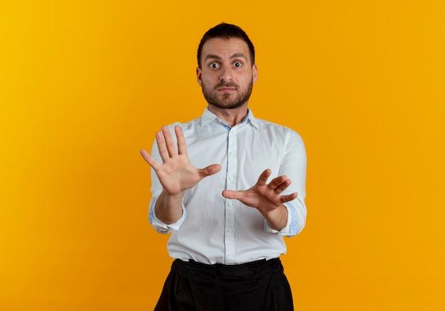 Geschokt knappe man staat met opgeheven handen op zoek geïsoleerd op oranje muur