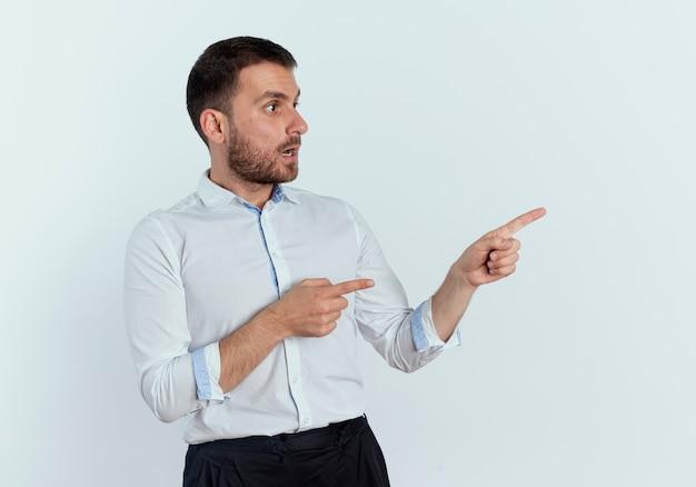 Geschokt knappe man wijst en kijkt naar kant geïsoleerd op een witte muur
