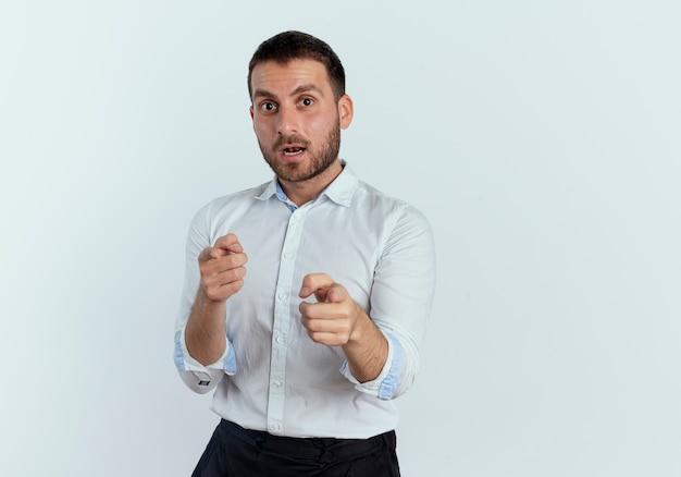 Geschokt knappe man wijst met twee handen geïsoleerd op een witte muur