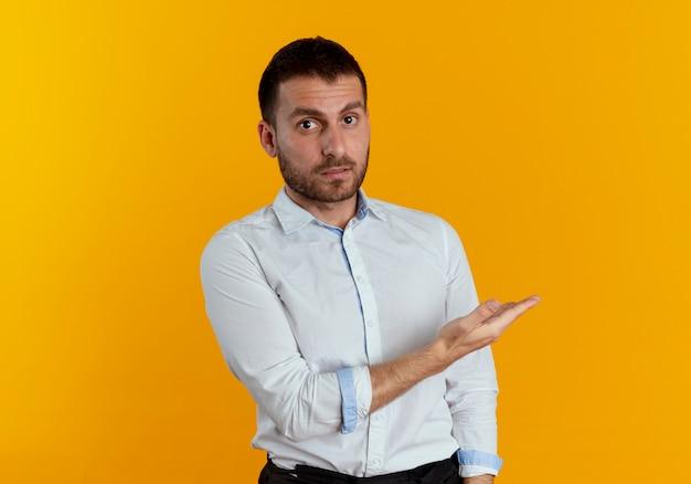 Geschokt knappe man wijst naar kant kijken geïsoleerd op oranje muur