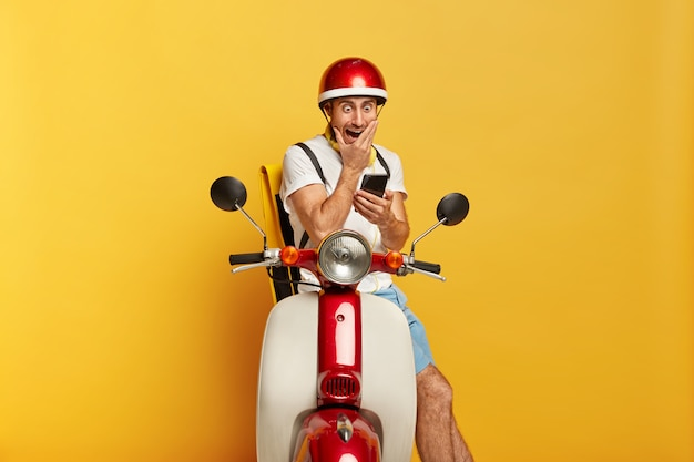 Geschokt knappe mannelijke bestuurder op scooter met rode helm