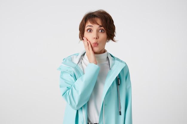 Geschokt kortharige jonge dame in witte golf en blauwe regenjas, staat op witte achtergrond met verbaasde uitdrukking, raakt wang, kijkt naar de camera met wijd open ogen.