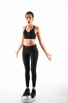 Geschokt krullend brunette fitness vrouw