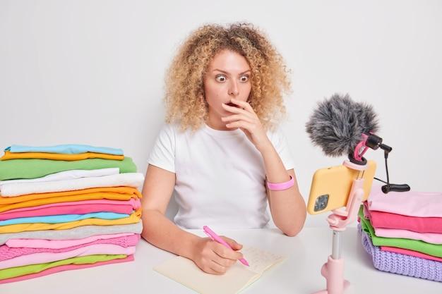 Geschokt krullend haired vrouw staart naar smartphone webcam ontdekt verbazingwekkende nieuws maakt notities in kladblok zit aan tafel met twee stapels gevouwen wasgoed geïsoleerd over wit