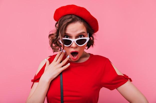 Geschokt krullende franse vrouw op zoek. emotionele europese dame in baret geïsoleerd.