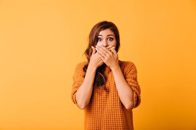 Geschokt leuk meisje dat mond behandelt met handen. studio shot van emotionele blanke dame geïsoleerd op fel oranje.