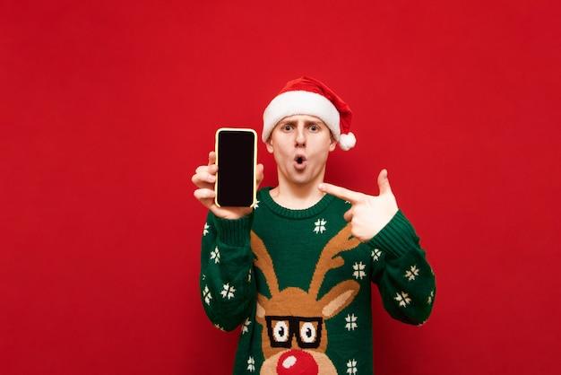 Geschokt man in kerstmuts en groene trui toont zijn vinger op smartphone scherm en kijkt in de camera met verbaasd gezicht op rood