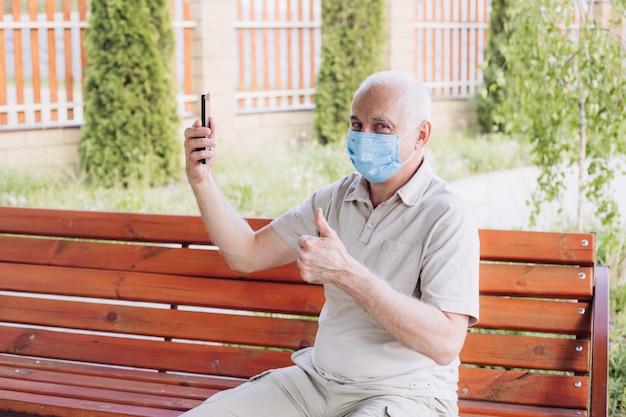 Geschokt man met medische gezichtsmasker met behulp van de telefoon naar nieuws te zoeken en tumb opdagen