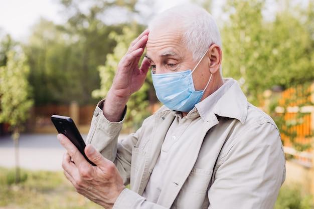 Geschokt man met medische gezichtsmasker met behulp van de telefoon om te zoeken naar nieuws