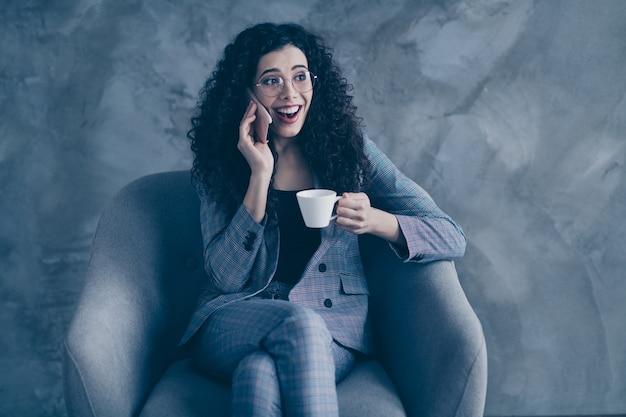 Geschokt manager meisje zit stoel drink koffie praten over telefoon geïsoleerd over grijze achtergrond
