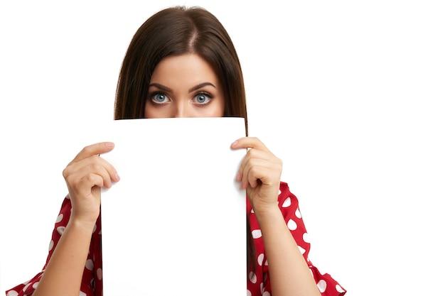 Geschokt meisje dat haar gezicht bedekt met een vel papier dat op wit wordt geïsoleerd