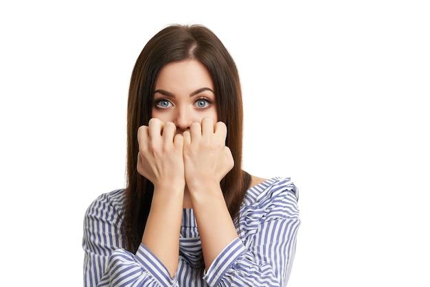 Geschokt meisje dat haar gezicht bedekt met handen die op wit worden geïsoleerd