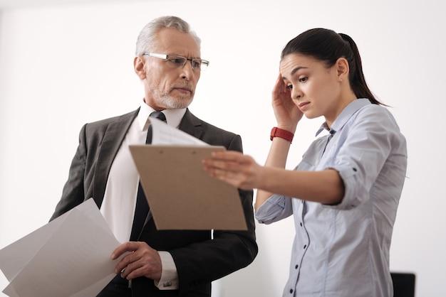 Geschokt meisje haar voorhoofd bedrijf map met documenten rimpelen permanent in halve positie