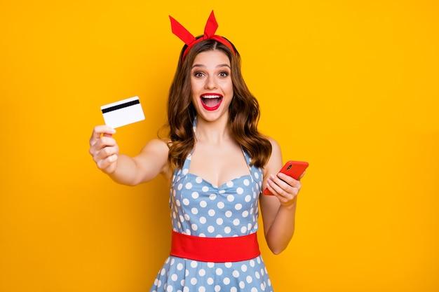 Geschokt meisje houdt mobiele telefoon toont plastic kaart draagt blauwe gestippelde jurk rode hoofdband