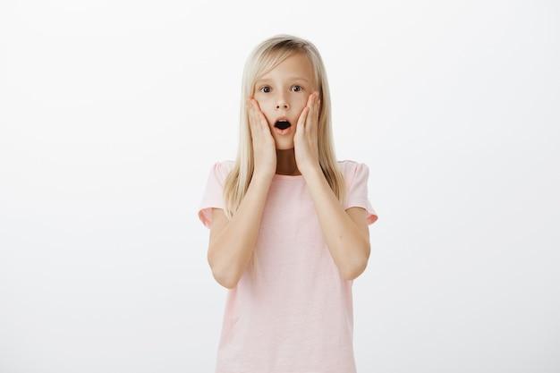 Geschokt meisje laat haar kaak vallen en staart onder de indruk