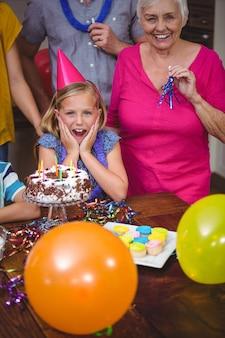Geschokt meisje met familie het vieren verjaardag