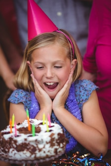 Geschokt meisje met verjaardagstaart
