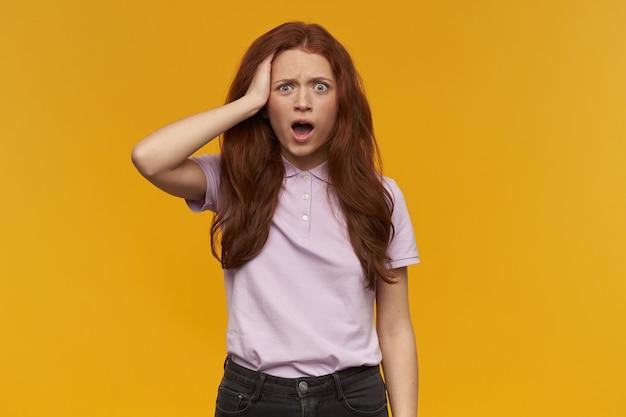 Geschokt meisje, verwarde roodharige vrouw met lang haar. roze t-shirt dragen. mensen en emotie concept. haar hoofd aanraken, iets vergeten. geïsoleerd over oranje muur
