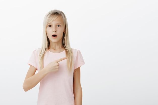 Geschokt meisje wijst naar rechts en laat verbaasde kaak vallen