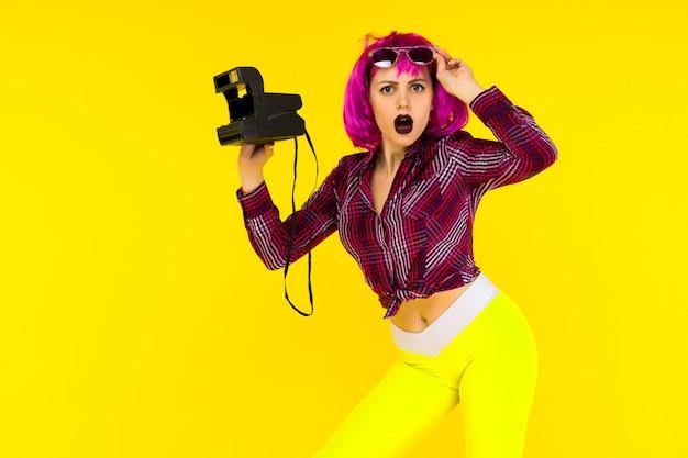 Geschokt meisjesportret met camera op gele achtergrond