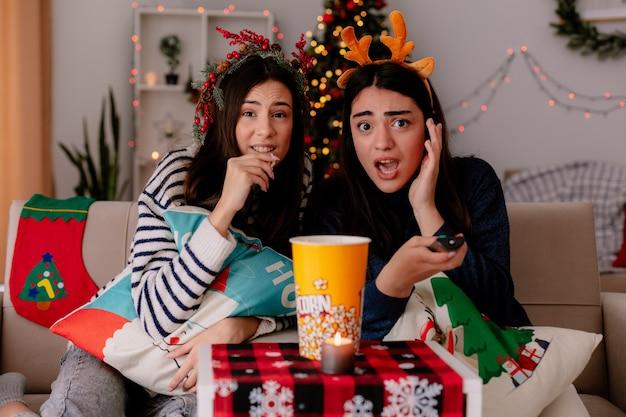 Geschokt mooi jong meisje met rendierhoofdband houdt tv op afstand zittend op een fauteuil met haar vriend die popcorn eet en thuis geniet van kersttijd time