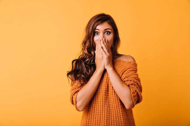 Geschokt mooi meisje in oranje kledij die gezicht bedekt met handen. indoor portret van charmante witte dame poseren op geel met verbazing.