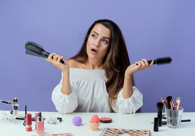 Geschokt mooi meisje zit aan tafel met make-up tools houdt haar kammen kijken kant geïsoleerd op paarse muur
