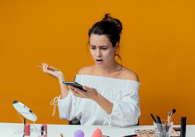 Geschokt mooi meisje zit aan tafel met make-up tools kijken naar telefoon met make-up borstel geïsoleerd op oranje muur